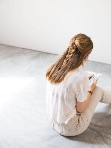 Chica sentada de espaldas mirando el móvil en una habitación de diseño minimalista con suelo de hormigón. Poppyns Magazine