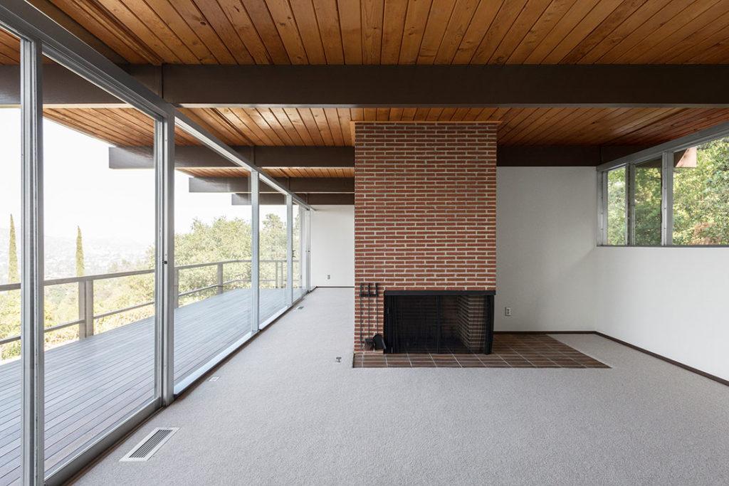 Chimenea de ladrillo caravista en habitación diáfana con moqueta, techo de madera, vigas de forja y ventanales que dan a una terraza entre árboles. Poppyns Magazine