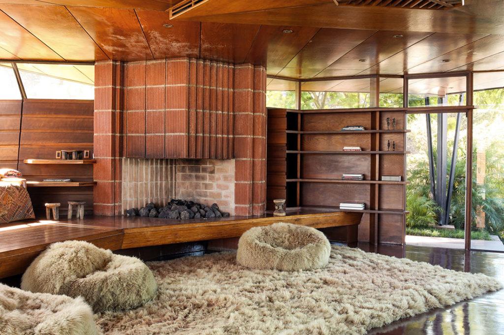 Chimenea de ladrillo de obra en habitación de diseño panelada en madera, una cristalera que da a un jardín y alfombra de pelo. Poppyns Magazine