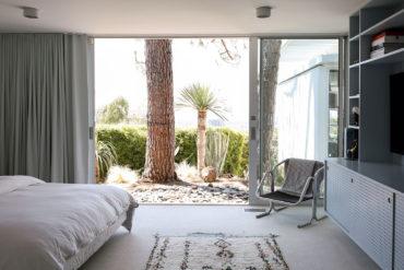 Dormitorio decorado estilo nórdico con muebles de diseño y un ventanal corredero que da a un jardín con piedras y vegetación. Poppyns Magazine