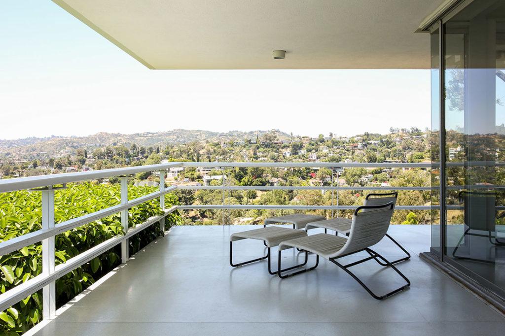 Tumbonas y reposapies de diseño de mimbre con forja en una terraza con vistas a la montaña. Poppyns Magazine