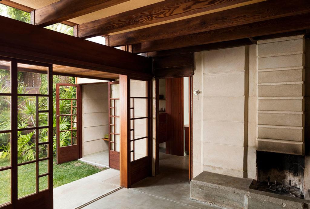Habitación con suelo y paredes de cemento, vigas de madera y cristalera con rasgos asiáticos con acceso a un jardín con césped y plantas. Poppyns Magazine