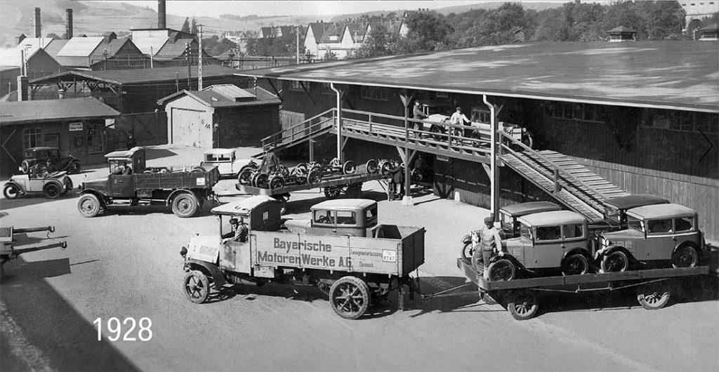 Foto en blanco y negro con coches BMW de época transportados por una camioneta con letras Bayerische Motoren Werke A.G en 1928. Poppyns Magazine