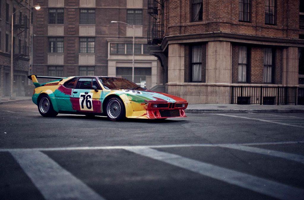 Coche BMW deportivo con la carrocería pintada con colores rojo, amarillo, azul y verde, con el número 76 en la puerta, un alerón en la parte trasera, circulando por una calle desierta. Poppyns Magazine