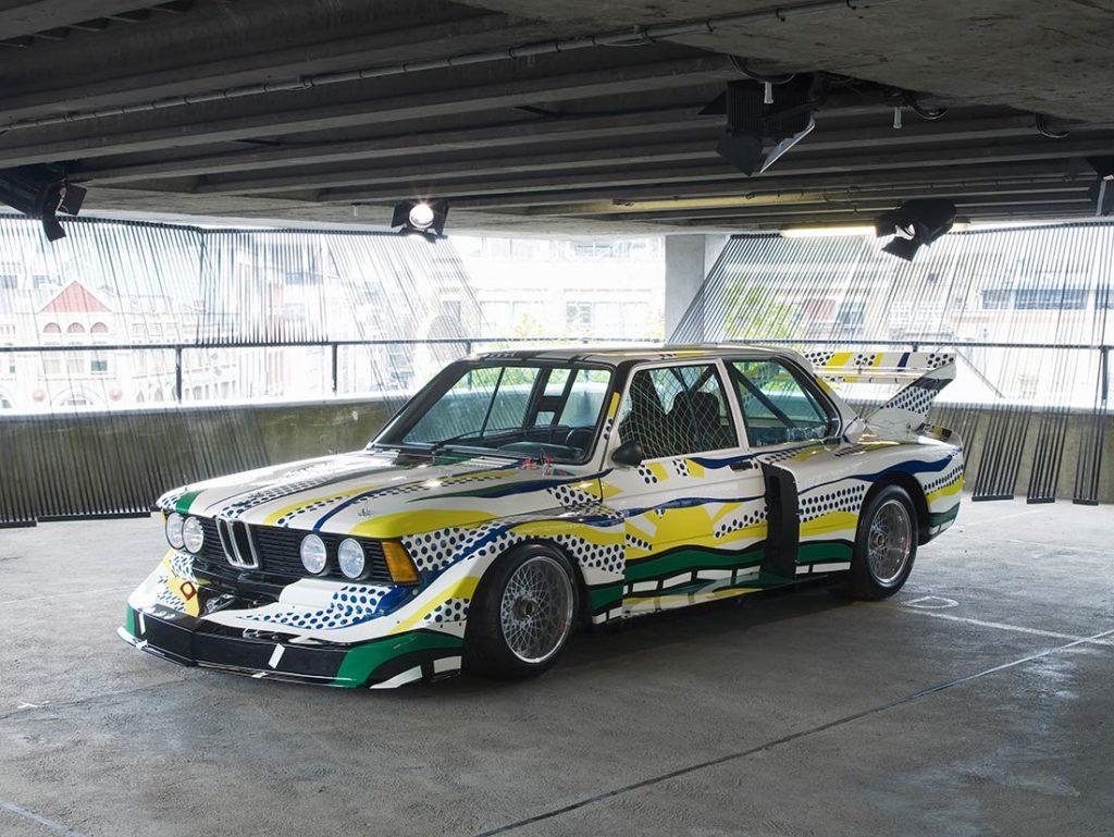 Coche BMW M3 deportivo blanco rotulado para competición a motas azules, rayas amarillas y una puesta de sol dibujada en el latera, con un alerón en la parte trasera, aparcado en un garaje. Poppyns Magazine