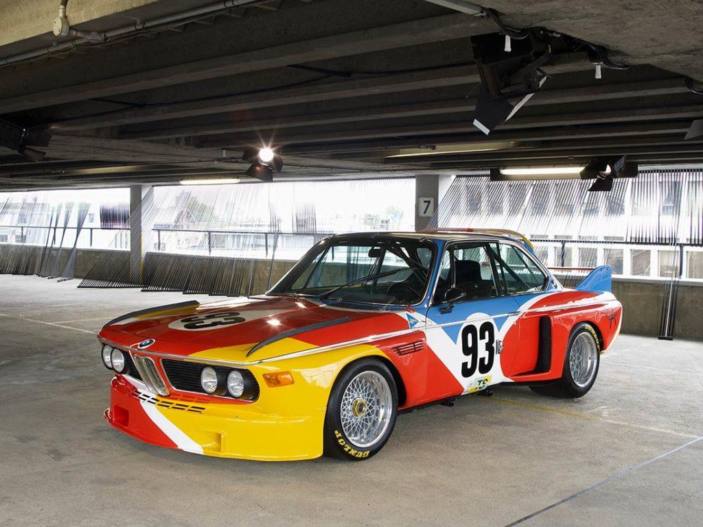 Coche BMW M3 deportivo rotulado para competición, con colores rojo, amarillo, blanco y azul, con el número 93 y ruedas Dunlop, aparcado en un garaje. Poppyns Magazine