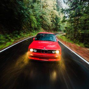 BMW M3 rojo circulando lloviendo por una carretera de montaña entre árboles. Poppyns Magazine