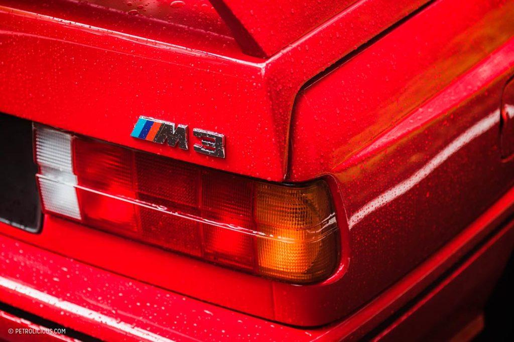 Detalle de la parte trasera de un BMW M3 rojo. Poppyns Magazine