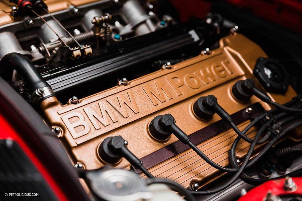 Detalle del motor de un BMW M3 rojo donde pone BMW M Power. Poppyns Magazine