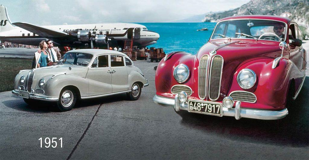 Dos coches BMW de los años 50, uno rojo y otro gris, junto a dos personas y un avión al fondo junto al mar. Poppyns Magazine