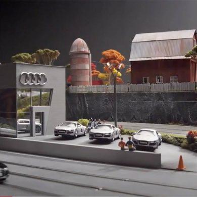 Maqueta de concesionario audi con exposición de coches, con una granja al fondo y árboles. Poppyns Magazine