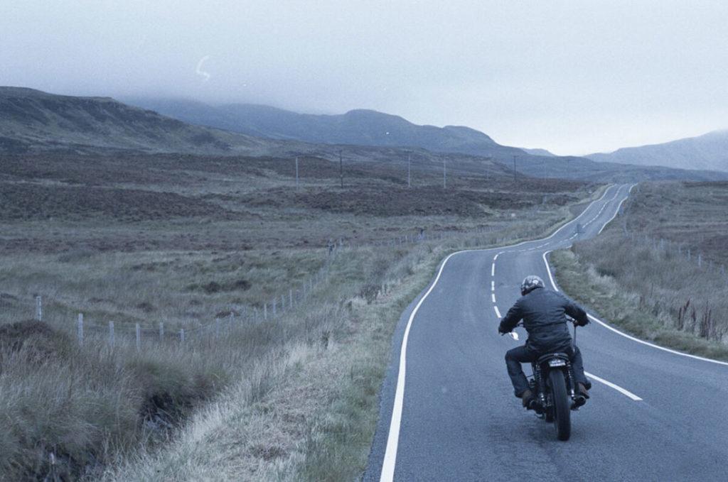 Motero con chupa de cuero negra conduciendo por carretera de asfalto entre montañas y prado verde. Poppyns Magazine