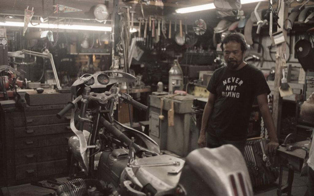 Taller de motos lleno de herramientas con moto despiezada y mecánico con rasgos asiáticos con camiseta de letras never not riding. Poppyns Magazine