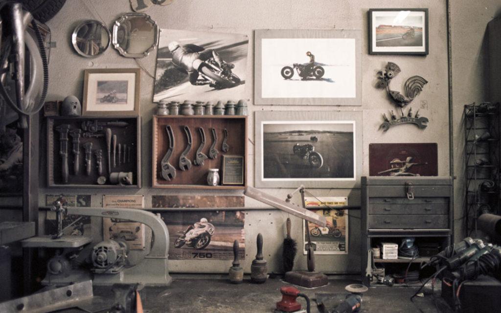 Pared de un taller de motos con cuadros y fotos de motos, herramientas y una mesa de trabajo. Poppyns Magazine