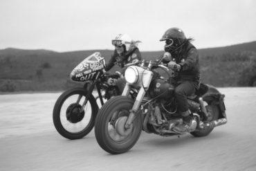Foto en blanco y negro de dos moteros con motos customizadas rodando por una carretera de tierra con montañas al fondo. Poppyns Magazine
