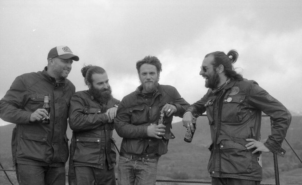 Foto en blanco y negro de cuatro moteros sonriendo apoyados en una vaya tomándose una cerveza en un lugar de montaña. Poppyns Magazine