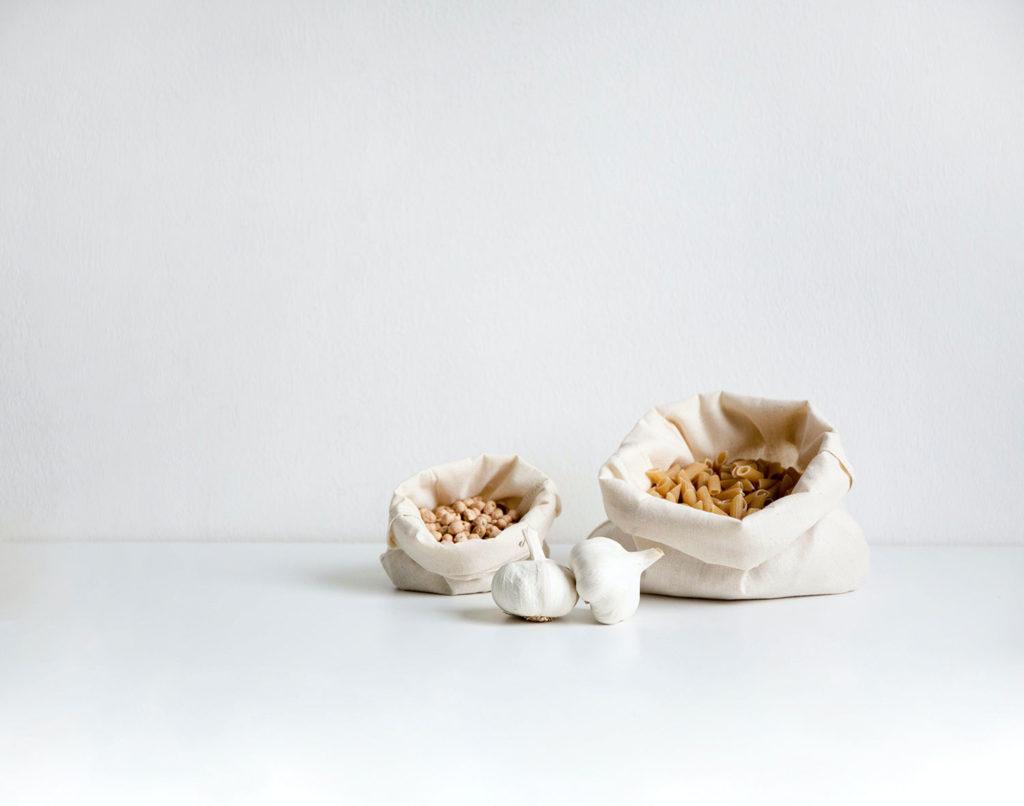 Bolsas de tela blanca con pasta y garbanzos junto con dos ajos. Poppyns Magazine