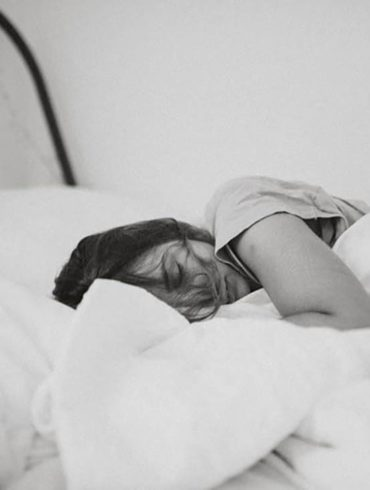 Foto en blanco y negro de mujer durmiendo en la cama de lado tapada con el edredón. Poppyns Magazine