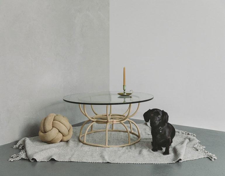 Mesa redonda de cristal sobre estructura tubular metálica, junto con un perro negro. Poppyns Magazine