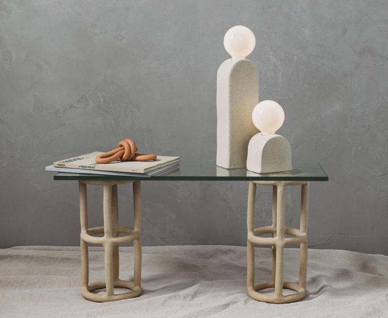 Mesa de cristal rectangular sobre estructura metálica, con dos lámparas y revistas sobre la mesa. Poppyns Magazine