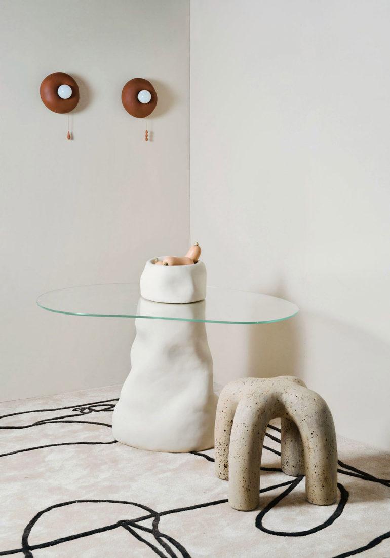 Mesa de cristal con estructura con forma orgánica blanca con un macetero blanco con calabazas, junto a un taburete con cuatro patas, sobre una alfombra blanca y dos lámparas de pared. Poppyns Magazine
