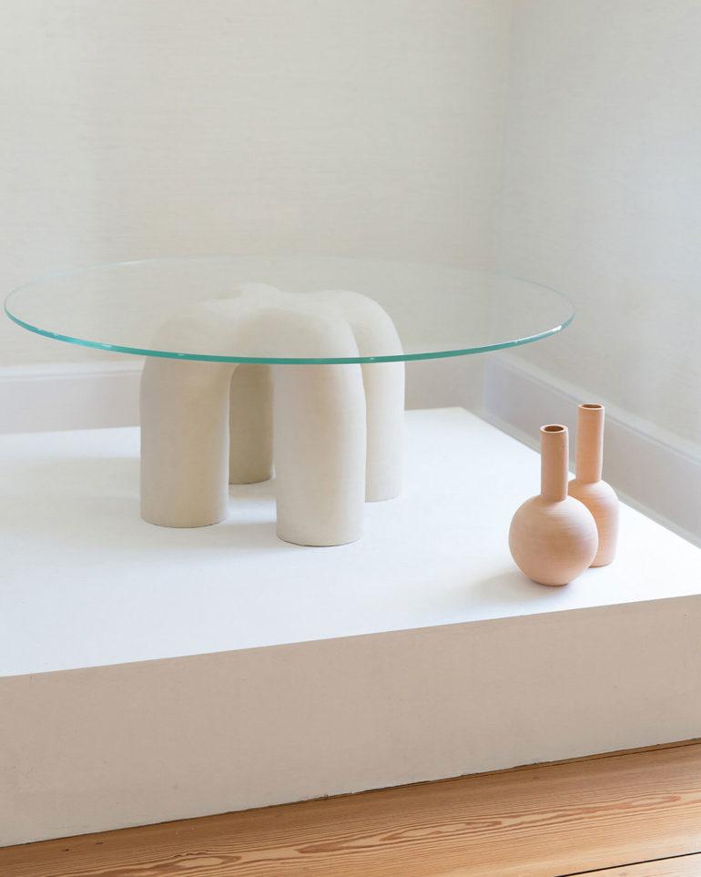 Mesa circular de cristal con patas de cerámica blanca en forma de herradura, junto a dos jarrones de cerámica marrón sobre una tarima blanca y suelo de madera. Poppyns Magazine