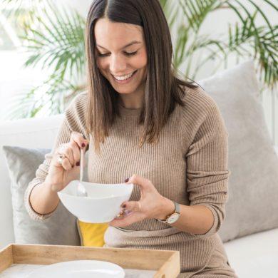 Mujer morena sonriendo sentada en un sofá comiendo de un bowl con una bandeja de madera. Poppyns Magazine