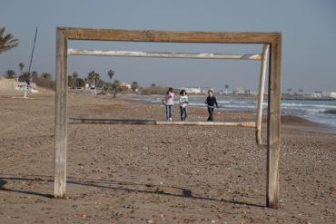 Portería de fútbol de madera en la playa con tres niñas paseando detrás. Poppyns Magazine