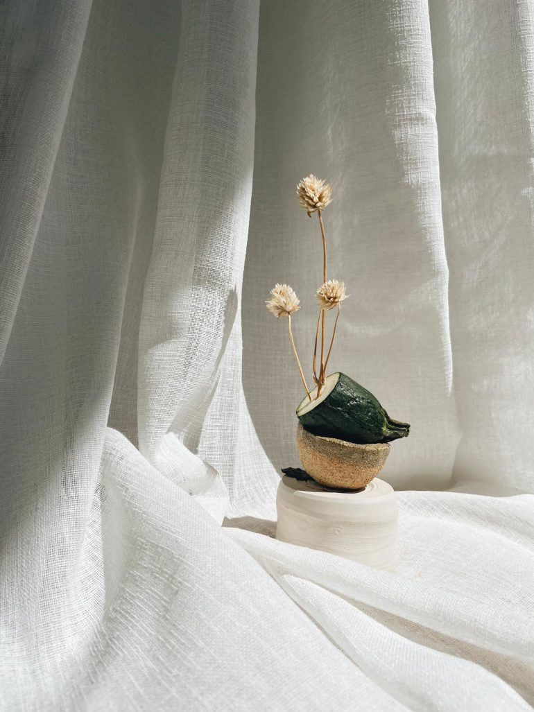 Composición en forma de bodegón de tres elementos sobre una cortina de lino blanco. En la base una pieza cilíndrica de arcilla blanca, encima media esfera de madera, sobre ella medio calabacín y coronado por una planta. Poppyns Magazine