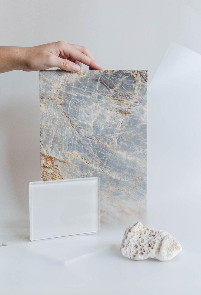 Composición en forma de bodegón de diferentes materiales con diferentes formas. Entre ellos una pieza rectangular de mármol, una pieza rectangular de cristal, una lámina de plástico transparente y una piedra blanca erosionada en primer plano. Poppyns Magazine