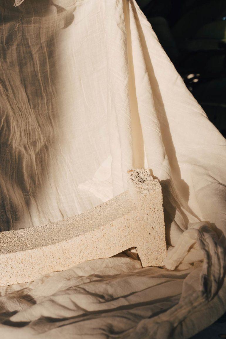 Pieza de piedra blanca con forma curva sobre una tela blanca. Poppyns Magazine
