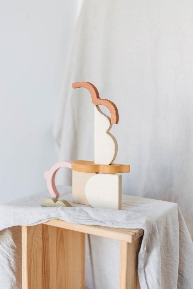 Composición en forma de bodegón de elementos de madera natural y lacada en blanco sobre una mesa de madera con un mantel de lino. Poppyns Magazine