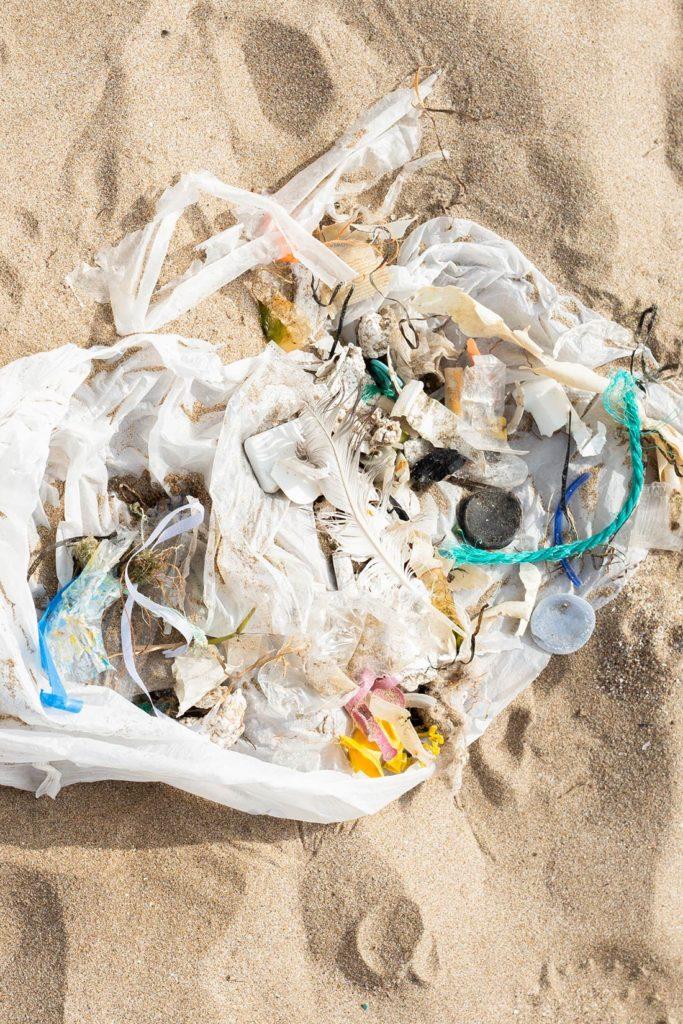 Bolsa de plástico con residuos plásticos recogidos en la arena de una playa. Poppyns Magazine