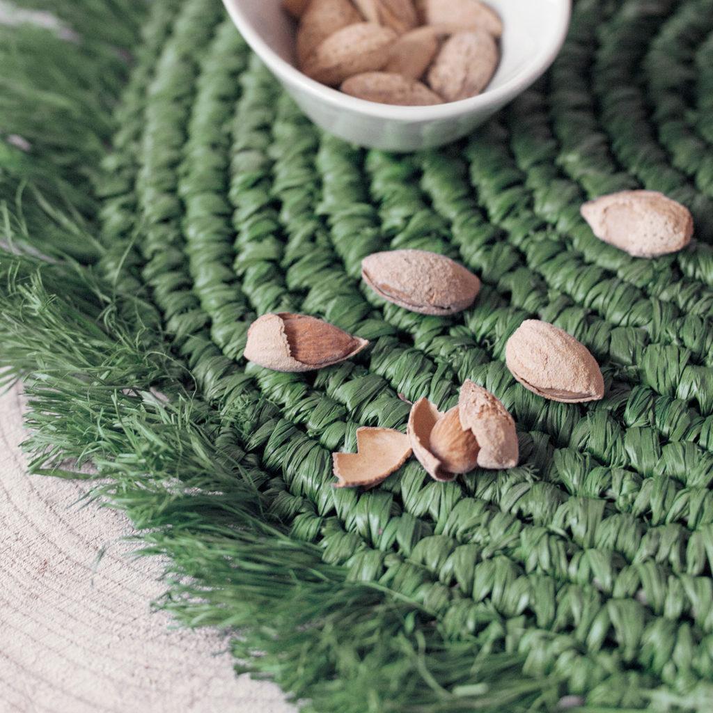 Almendras con cáscara sobre un mantel de esparto verde. Poppyns Magazine