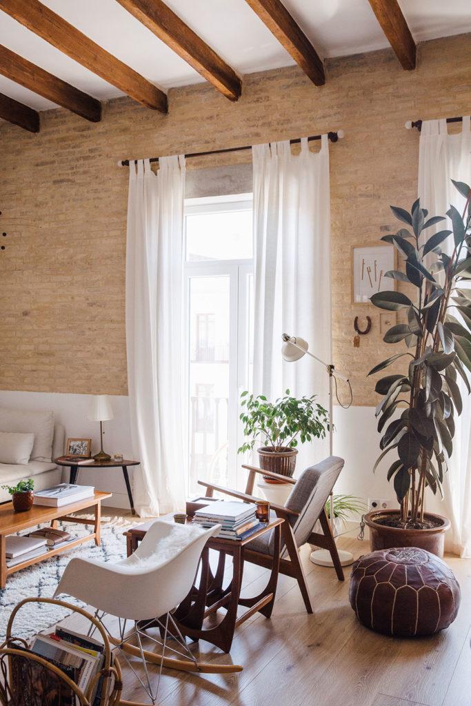 Salón con parquet, paredes de ladrillo caravista y techos con vigas de madera vistas, cortinas blancas, un puff y mobiliario de diseño. Poppyns Magazine