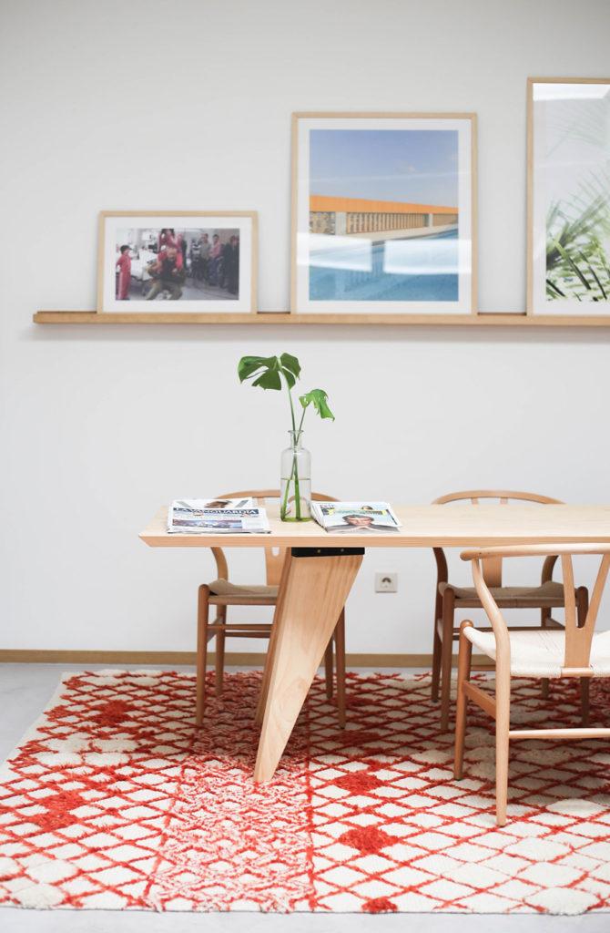 Mesa de diseño de madera con sillas vintage sobre una alfombra roja y unos cuadros al fondo. Poppyns Magazine