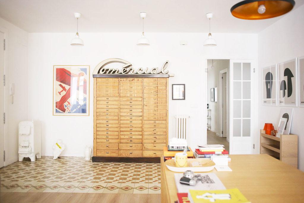 Habitación con suelo de mosaico, paredes blancas y muebles vintage. Poppyns Magazine