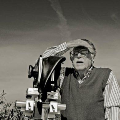 Foto en blanco y negro de un señor mayor con gafas, bigote, camisa a rayas y chaleco, mirando al horizonte tapándose el sol con la mano, junto a una cámara de fotos. Poppyns Magazine
