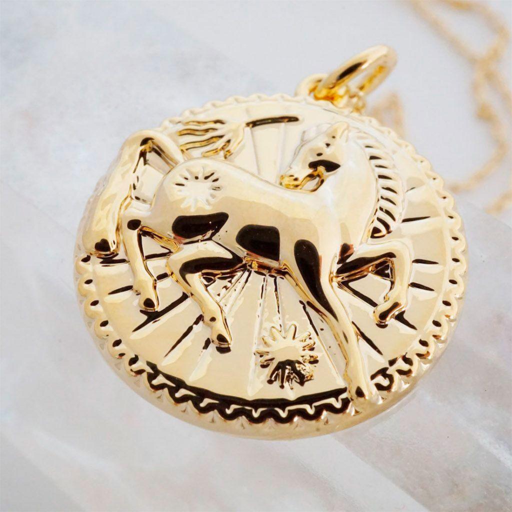 Medallón de oro con un caballo en el centro. Poppyns Magazine