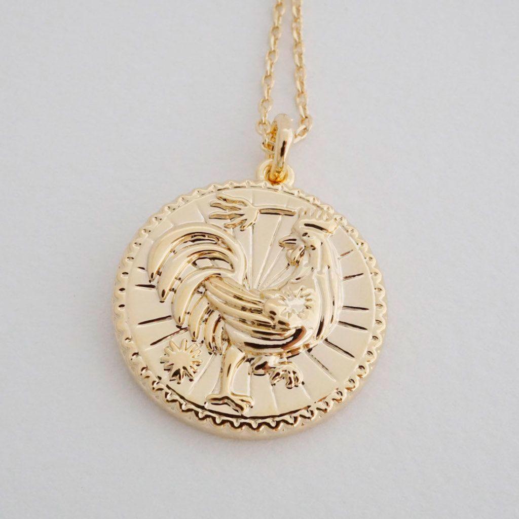 Medallón de oro con un gallo en el centro. Poppyns Magazine