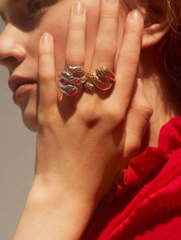 Mujer rubia con vestido rojo llevando dos anillos de serpientes de oro y plata en la mano. Poppyns Magazine