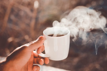 Mano sujetando una taza de café humeante. Poppyns Magazine