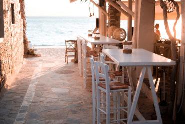 Terraza con sillas altas de madera blanca y mimbre en un restaurante a pie de mar en una calle empedrada. Poppyns Magazine