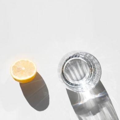 Vaso de de cristal lleno de agua junto con un limón y sus sombras proyectadas. Poppyns Magazine