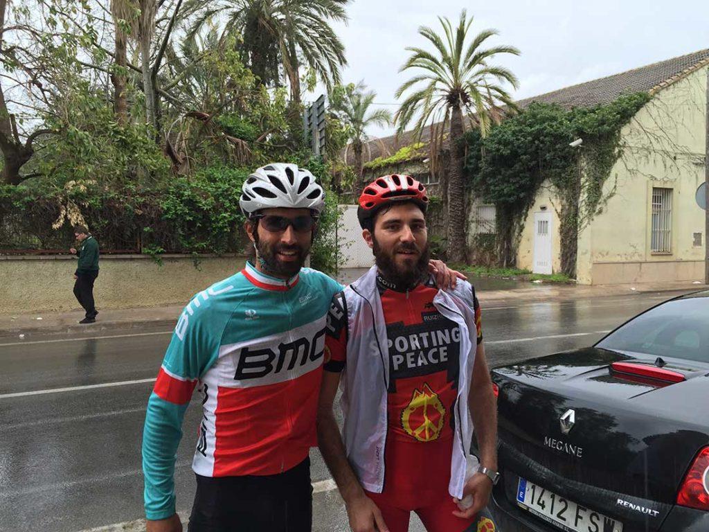 Dos hombres con barba vestidos de ciclista posando para una foto bajo la lluvia. Poppyns Magazine
