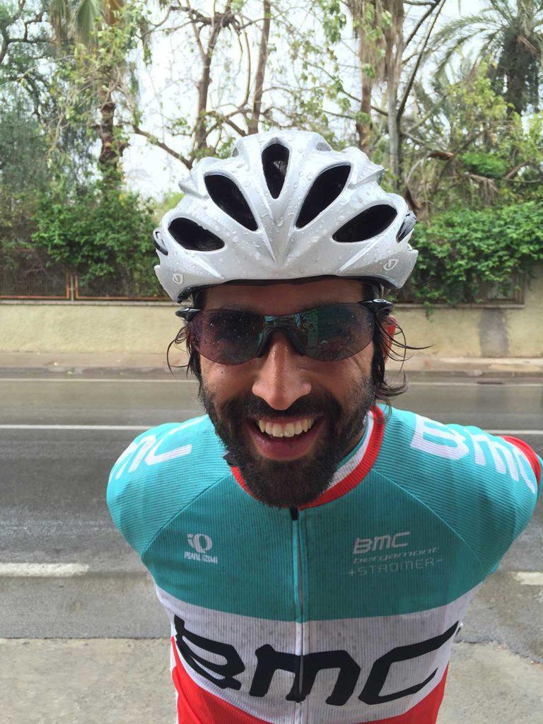 Ciclista sonriendo con barba, mallot, gafas de sol y casco blanco mojados por la lluvia. Poppyns Magazine