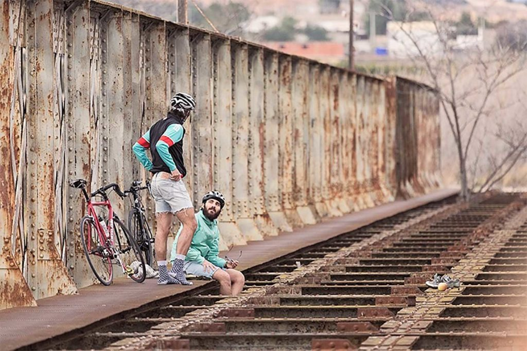 Dos ciclistas hablando sentados en la vía de un tren con las bicis apoyadas en una estructura metálica. Poppyns Magazine