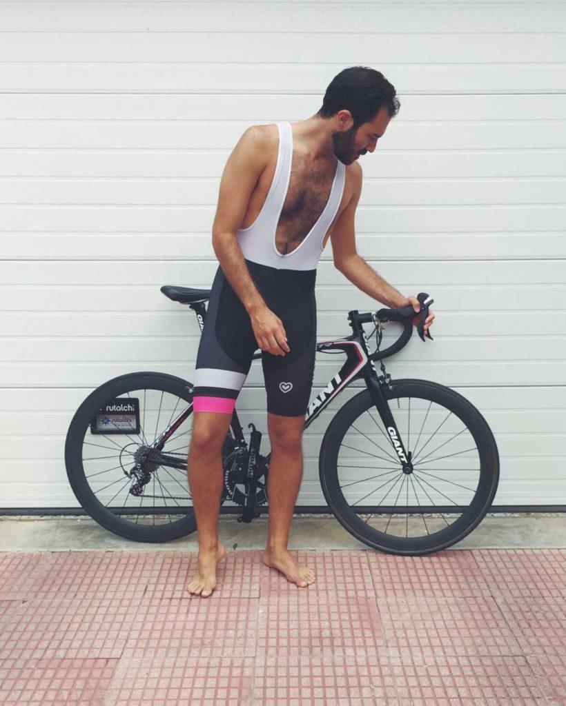 Hombre vestido de ciclista, descalzo cogiendo el manillar de una bici apoyada en una puerta blanca de un garage. Poppyns Magazine