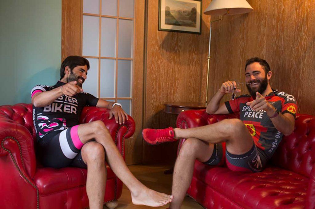 Dos hombres vestidos con ropa ciclista sentados en un sofá rojo riéndose. Poppyns Magazine