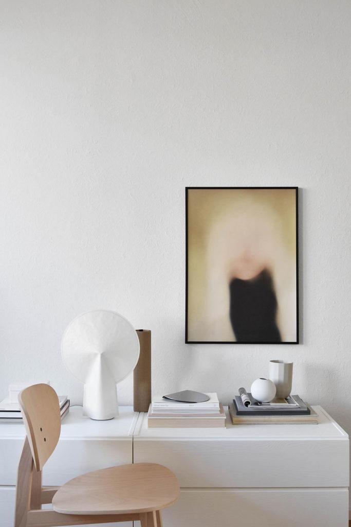 Aparador blanco de madera con elementos de diseño, una silla de madera de diseño y un cuadro con un rostro difuminado en la pared. Poppyns Magazine
